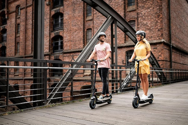 Frau und Mann fahren mit E-Scooter